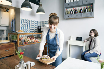 Waitress holding wooden board with sandwich