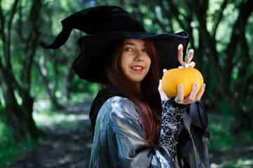 Portrait of young witch with pumpkin