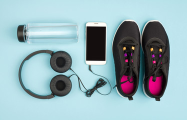 Fitness objects isolated on blue background. Sneakers, water and audioplayer