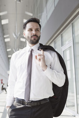 Businessman with hands in pockets in airport