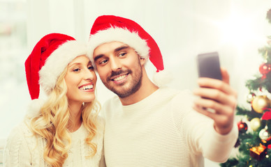 couple taking selfie with smartphone at christmas