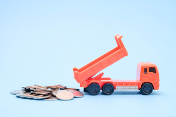 save money for investment concept truck toy and Coins on blue background