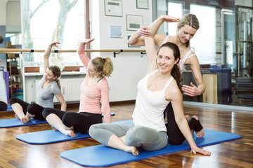 Instructor supports women stretching arms in Pilates class