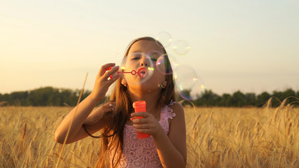 girl walks in the field and blows bubbles.