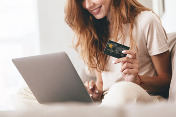 Cropped picture of lady using laptop computer holding credit card.
