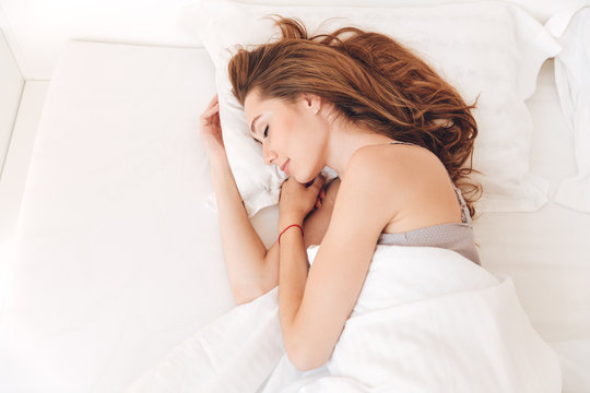 Smiling pretty lady sleep in bed indoors. Eyes closed.