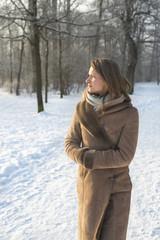 Young woman in coat walking in winter landscape