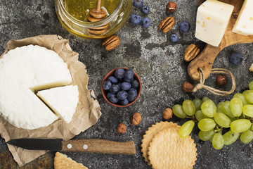 Young white cheese, a new recipe for cheese with fenugreek, a hard chopped Parmesan on a gray stone background with blueberries, nuts, green grapes, honey. Top view. Selective focus..