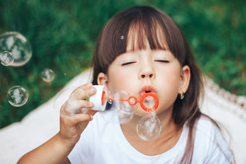 little girl blowing bubble to camera close up
