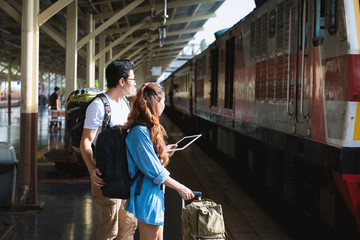 Couple traveler hold tablet look at the train