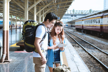 couple asian woman and asian man traveler looking the map in tablet with train station background. Travel in summer concept