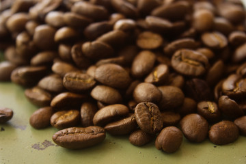 close up coffee beans on green metallic surface