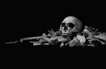 Skull on pile bone on black background, dim light in Halloween night Style black and white