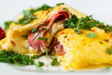 Fluffy stuffed egg omelette with ham, cheese and green herb, closeup.
