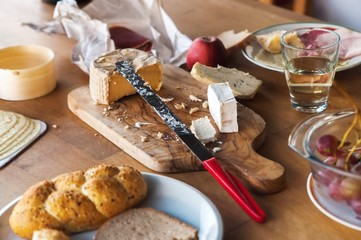 Wooden table with cheese, bread, ham and fruit