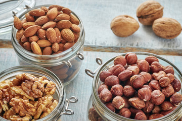 Walnuts, hazelnuts and almonds in jars on a rustic wooden background, shallow depth of field.