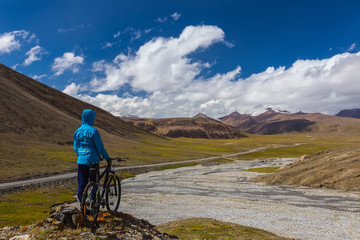 A guy with a bicycle on the background of high mountains. Suek Pass. Arabelso Valley. Kyrgyzstan.