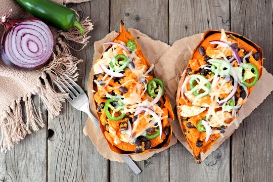 Baked sweet potatoes stuffed with chicken, vegetables and cheese, above view on a rustic wood background