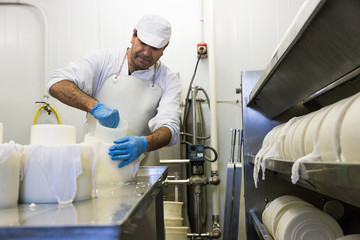 Adult man in special uniform standing at table in factory shop and working with cheese production.