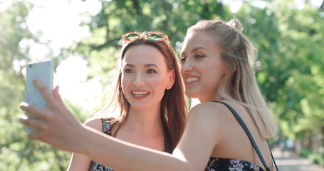 Close up portrait of two young cheerful girls having fun and making selfie, outdoors. Two beautiful teenage girls using phone in a city park.