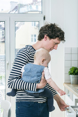 Father tending baby in kitchen