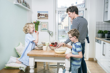 Father and children in kitchen preparing food