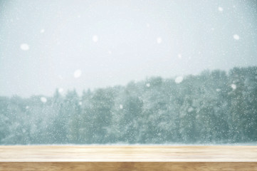 Christmas and New year background. Wooden table with winter snowfall covered forest. Vintage color tone and rustic style.