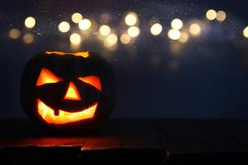 Halloween Pumpkin on wooden table in front of spooky dark background. Jack o lantern