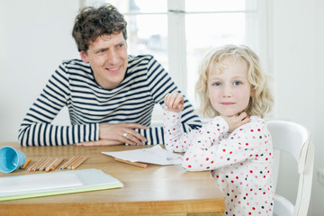 Father and daughter coloring a book