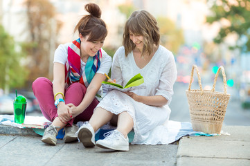 two girls are sitting, writing