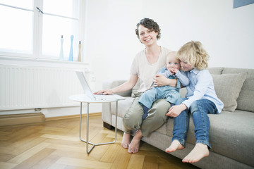 Mother and children with laptop in living room