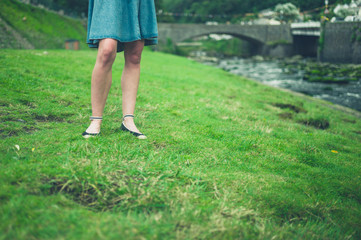 Legs of young woman standing by river