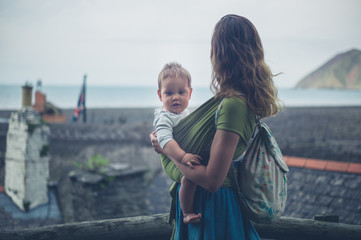 Mother with baby looking at town and the sea