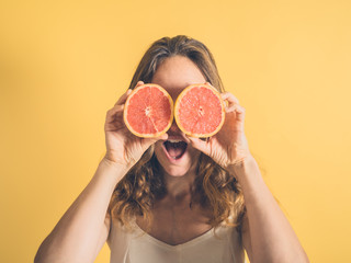 Silly woman using grapefruit as binoculars