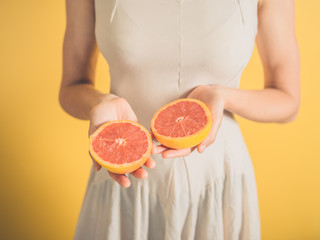 Woman with grapefruit halves