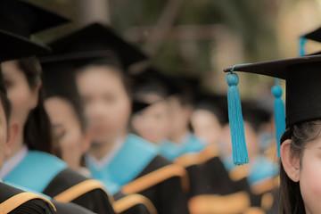 Graduates in commencement graduation ceremony row, metaphor education, success, concept, background with copy space, selective focus on graduation cap