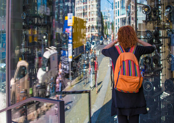 in a city looks a woman interested in shop window
