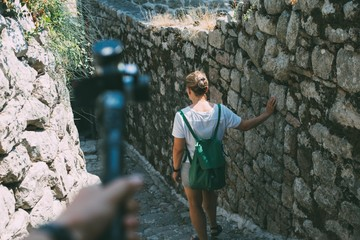 Middle aged female traveler walks on streets filled with bricks and unfocused hand holding a stabilizer with action camera attached to it