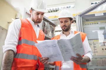 Two engineers checking electricity substation