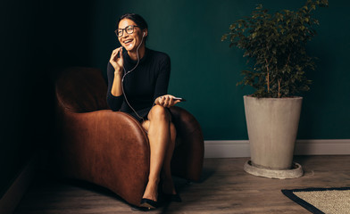 Smiling woman talking on smartphone, sitting on chaise lounge
