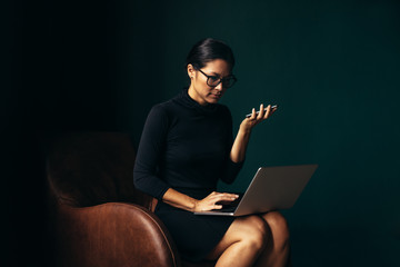 Young businesswoman using laptop and holding smartphone