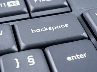 Gray keyboard with focus on backspace button and soft focus on back