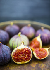 Ripe figs in the old bowl on a stone background. Still life.