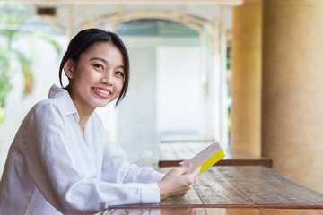 Asian woman reading book on the table with blurry background