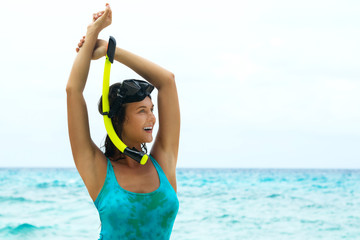 Happy woman on the beach with mask for snorkeling