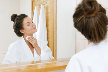 Woman is washing her face with lotion and cotton pads