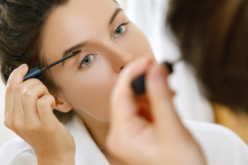 Woman applying tinted eyebrow gel