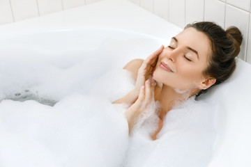 Woman is taking bath with a foam