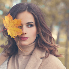 Autumn Beauty. Perfect Woman Fashion Model with Fall Mapple Leaf Outdoors