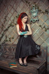 tattooed girl in a black dress, with orange dreadlocks. Girl reading a book, dreaming. The scenery in the Studio: the clock on the wall, old bench. The conceptual idea
